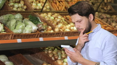 Man write in his notebook at the supermarket Stock Footage