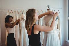 Female fashion designers adjusting the dress on mannequin Stock Photos