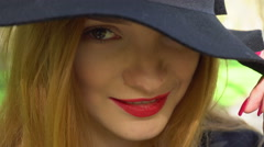 Woman with red lips and hat with wide brim smiling Stock Footage