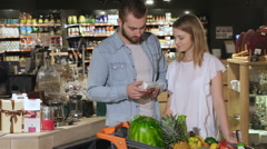 Couple choose tea at the hypermarket Stock Footage
