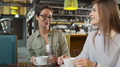 Two Young Women Talking at Cozy Coffee Shop Stock Footage