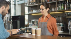 Handsome Young Man Paying for Takeaway Coffee with Mobile Phone at Coffee Shop. Stock Footage