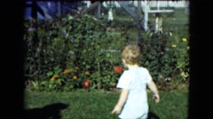 1951: an adult off-camera is blowing bubbles for a toddler boy in the backyard Stock Footage