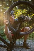 Male cyclist repairing his bicycle in forest Stock Photos