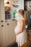Pregnant woman looking for food in refrigerator in kitchen Stock Photos