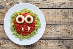 Green spaghetti pasta creative halloween food vampire monster with fake blood Stock Photos