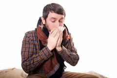 Pale sick man with a flu, sneezing, in a clean background Stock Photos