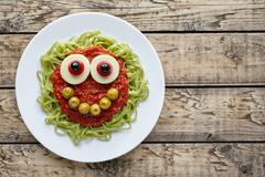 Green spaghetti pasta creative halloween food monster with cute smile and big Stock Photos