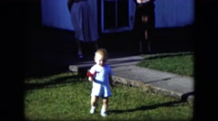 1951: a cute little toddler walking through the yard holding a red flower Stock Footage