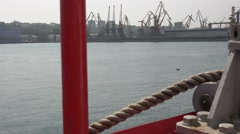 Mooring bollard with rope on ship on background of shipbuilding cranes Stock Footage