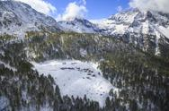 Aerial view of the alpine village of Laguzzola framed by woods and snowy peaks, Stock Photos