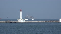 Ukrainian Navy Flagship warship passes through channel to port near lighthouse Stock Footage