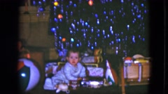 1951: baby plays with new toys and presents under tinseled tree on christmas Arkistovideo