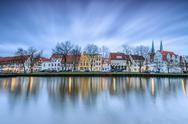 Clouds on the typical houses and towers of cathedral reflected in River Trave at Stock Photos