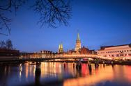 The lights of dusk on typical bridge and the cathedral reflected in River Trave, Stock Photos