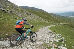 A mountain biker descends the trail from The Old Man of Coniston in the Lake Stock Photos