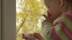 Little girl in striped sweater playing a game on the phone, sitting on the sill. Stock Footage