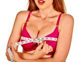 Girl in lingerie measures her breast measuring tape. Stock Photos