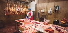 Butcher chopping meat in storage room Stock Photos
