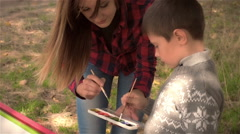 Mother and son paint on the paper Stock Footage