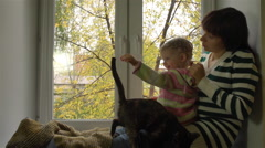 Mother braiding daughter's hair on the windowsill on a cloudy autumn day. Stock Footage
