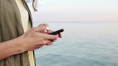 Side view of a woman in a green jacket and a yellow T-shirt holding a mobile  Stock Footage