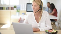 Busy customer service manager eating lunch in office Stock Footage