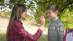 Mother paints on my son's face and they smile Stock Footage