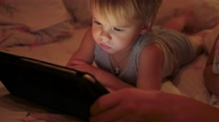 A little boy watches cartoons in the tablet late in the evening Stock Footage