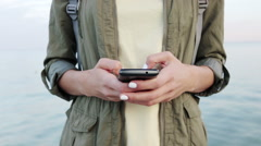 Close-up of a woman in a green jacket and a yellow T-shirt holding a mobile p Stock Footage