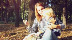 Young mother playing with her baby. Mom and son sitting on the grass in a park Arkistovideo
