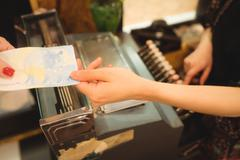 Female cashier accepting a payment at counter Stock Photos