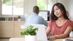 Young asian mixed-race woman working in office Stock Footage