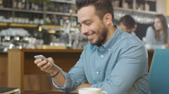 Hispanic Ethnicity Young Man using Mobile Phone at Cozy Coffee Shop. Stock Footage