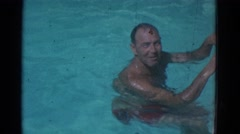 1953: man in red swimtrunks in swimming pool talking to video camera NEW YORK Stock Footage