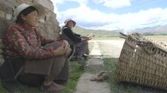 Old Tibetan people outside their ancient village Stock Footage