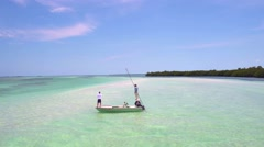 Drone view of people on boat fishing in clear ocean Stock Footage