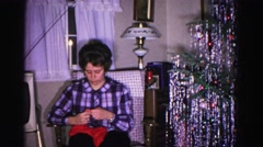1967: woman unwraps small christmas present while talking to someone off camera Stock Footage