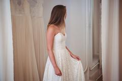Woman trying on wedding dress in a shop Stock Photos