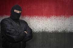 Dangerous man in a mask standing near a wall with painted national flag of ye Stock Photos