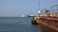 Rusty barge on background of harbor tug with yellow logging in seaport Stock Footage