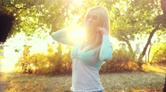 Romantic young woman with blond hair in autumn Park on sunshine background Stock Footage