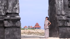 Young sexy lady  in a dress stay near the balinese gates and admires the view. Stock Footage