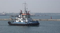 Harbor tracker with white wheelhouse runs along pier in seaport Stock Footage