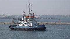 Harbor tracker with white wheelhouse runs along pier in seaport Stock Footage