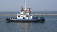Harbor tug with white wheelhouse runs along pier in seaport Stock Footage