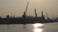 Sunset at port on background of cargo cranes with reflection in water Stock Footage