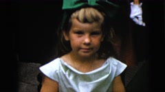 1962: a cute young girl with a dress and a wearing a big green bow in her hair Stock Footage