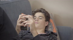 Teenage boy playing a game on his smartphone while relaxing on the couch. 4K UHD Stock Footage