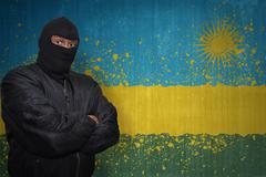 Dangerous man in a mask standing near a wall with painted national flag of rw Stock Photos